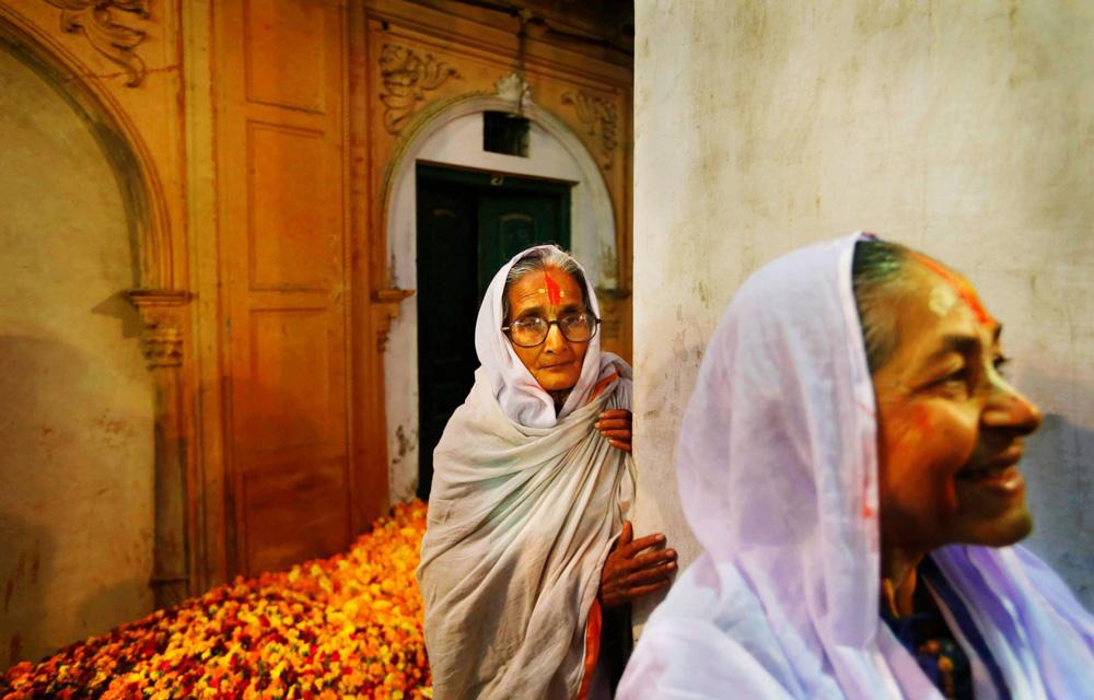 Widows wait for Holi celebrations to begin at the Meera Sahbhagini Ashram in Vrindavan.