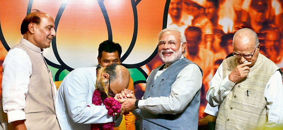 Leader: Amit Shah (centre), the newly appointed president of the BJP is congratulated by outgoing BJP president Rajnath Singh (right) and Prime Minister Narendra Modi