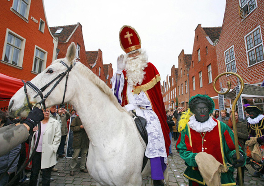 Sinterklaas (C) and his Zwarte Pieten (R
