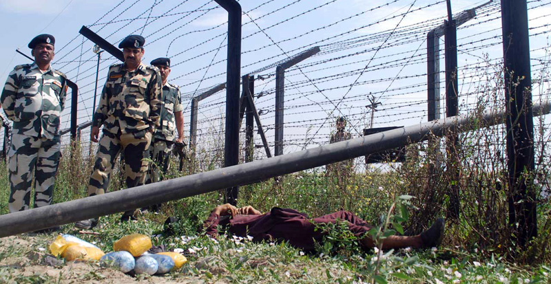 BSF personnel inspect the body of a Pakistani smuggler who was trying to cross the border with eight kg heroin worth 40 crore, Photo: Raman Gill