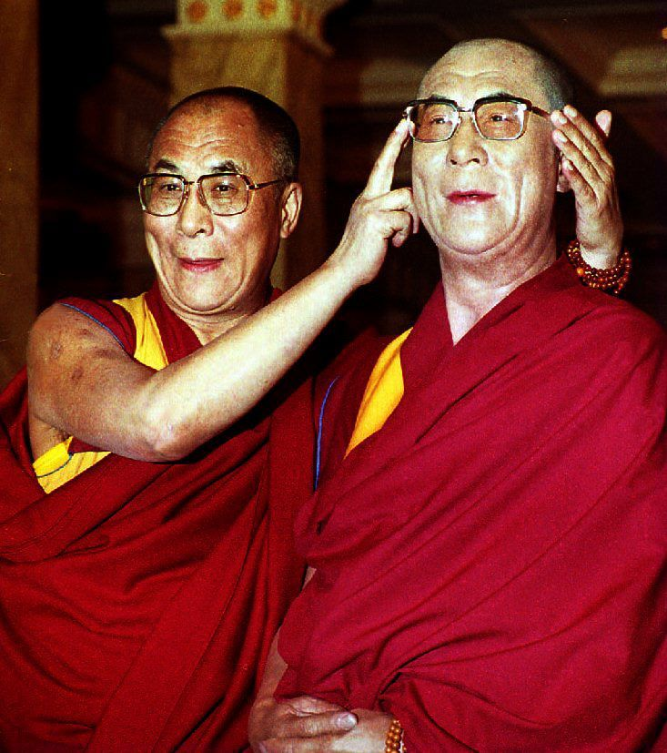 The Dalai Lama poses with his wax portrait in the
