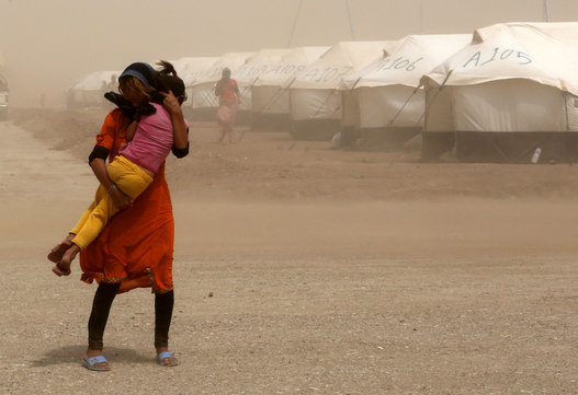 An internally displaced Iraqi woman holds her sister during a sandstorm outside the Bajid Kandala camp in Feeshkhabour, Iraq on Aug. 19, 2014. (AP Photo/Khalid Mohammed)
