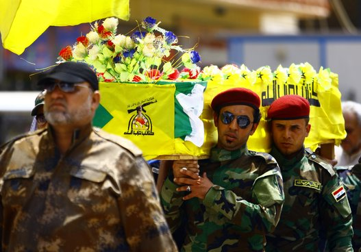 Members of the Hezbollah Brigade in Iraq, a Shiite movement supporting Iraqi government forces in the ongoing clashes against Islamic Sate (IS) jihadists in northern Iraq, carry the coffin of a comrade during his funeral procession on Aug. 20, 2014 in Najaf after he was killed in combat south of Baghdad. (HAIDAR HAMDANI/AFP/Getty Images)
