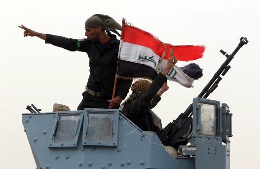 Members of Iraqi anti-terrorism forces wave the national flag in celebration after securing a checkpoint from Sunni militants in the village of Badriyah, west of Mosul, Iraq on Aug. 19, 2014. (AHMAD AL-RUBAYE/AFP/Getty Images)