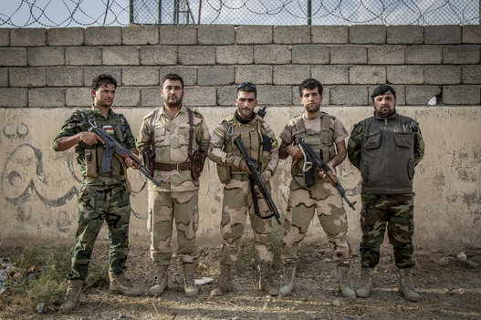 Peshmerga soldiers pose for a group portrait at a military base south of Erbil, the capital of the Kurdistan Regional Government in Iraq. (Vianney Le Caer/Pacific Press/LightRocket/Getty Images)