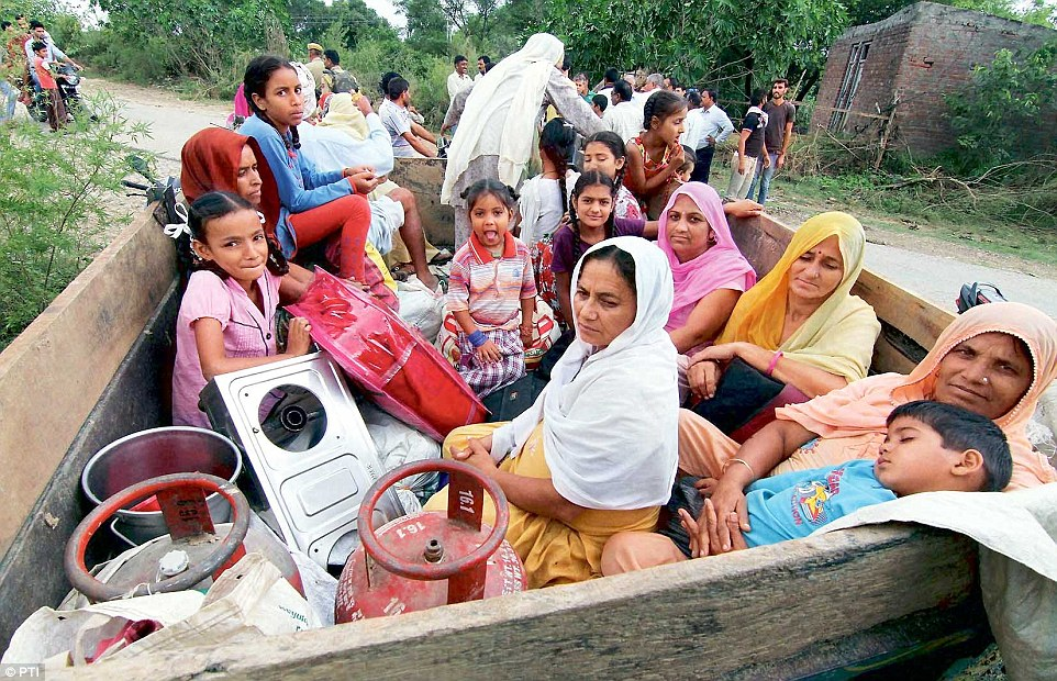 Residents of the Chilayari village in Samba district sit in a trailer as they prepare to leave the area following the death of two women who lived here.  Read more: http://www.dailymail.co.uk/indiahome/indianews/article-2785698/Islamabad-shocked-Indian-Army-launches-massive-retaliation-border-firing-confident-PM-Modi-promises-right-soon.html#ixzz3FcbE8Tbr  Follow us: @MailOnline on Twitter | DailyMail on Facebook