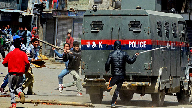 Protesters vandalise a police vehicle during a protest against government's plan for setting up separate township for Kashmiri Pandits, at Lal Chowk in Srinagar on Friday. (PTI Photo)