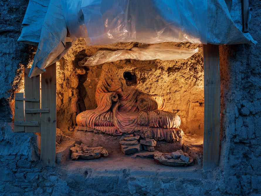 "Searching for treasure, looters ravaged this larger-than-life-size Buddha. ""Archaeology is the only way to protect the site,"" says Philippe Marquis, who oversaw excavation until 2014. PHOTOGRAPH BY SIMON NORFOLK"