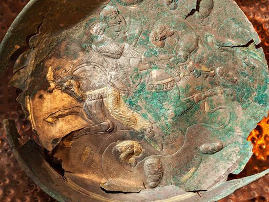A detail of a copper and gold bowl from Tepe Baba Wali at Mes Aynak depicts a snarling lion.