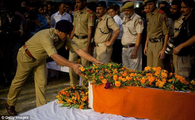 Honours: A senior Indian police officer lays a wreath on Altaf Ahmad Dar's coffin in Srinagar