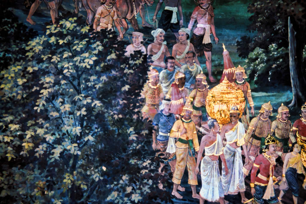 In this scene detail from a painted mural at the Emerald Buddha Temple, Bangkok, Thailand, baby Sita's golden urn is carried to the king's palace in a royal procession. The beautifully dressed king's courtiers, carrying the closed golden urn, pass from the back to the front of the right half of the image.